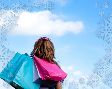 gratified: Woman holding shopping bags outdoor  against snowflake frame Stock Photo