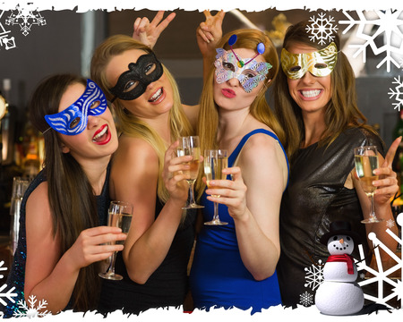 Attractive women wearing masks holding champagne against christmas themed frame
