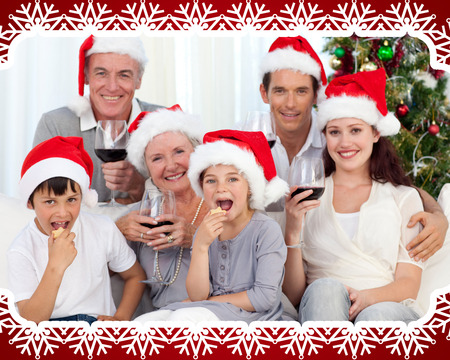 Family drinking wine and eating sweets in Christmas against snowflake frame photo
