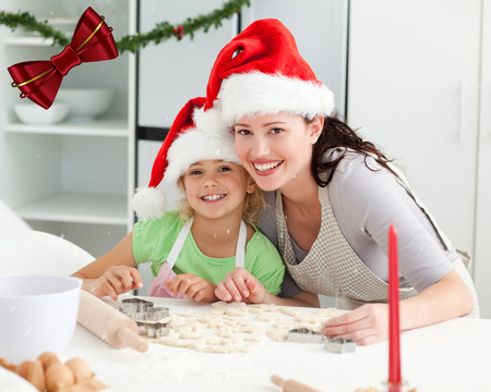 Portrait of a cute girl with her mother baking Christmas cookies against digitally generated red shiny bow photo