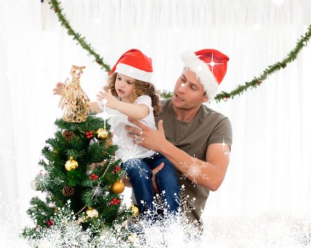 Cute daughter decorating the christmas tree with his father against snow photo