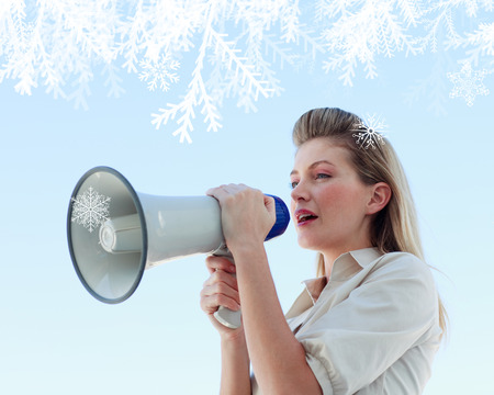 Blonde businesswoman shouting through megaphone against snowflakes photo