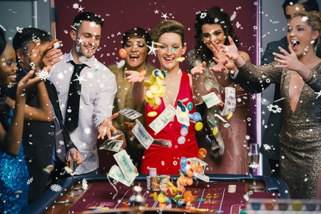 People throwing chips and cash on roulette table against snow falling photo