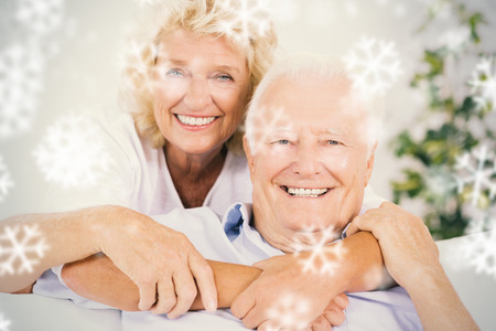 Composite image of happy old couple portrait hugging against snowflakes photo