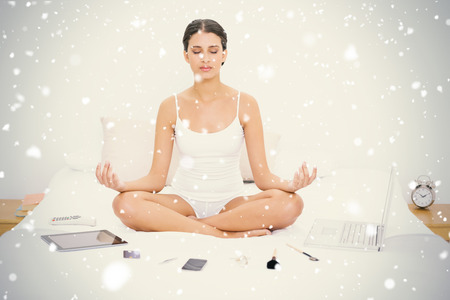 Natural young brown haired model in white pajamas practicing yoga against snow falling photo