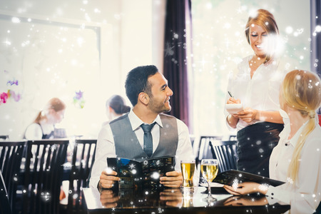 Composite image of business people ordering dinner against snow falling photo