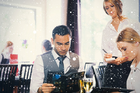 Handsome businessman reading the menu against snow falling photo