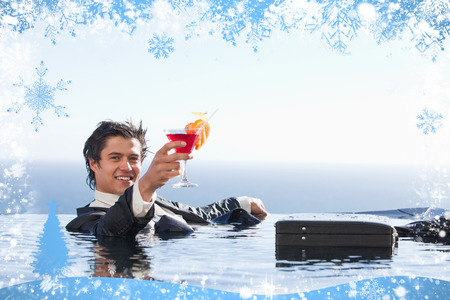 gentle dream vacation: Cheerful businessman relaxing in a swimming pool with a cocktail against snow