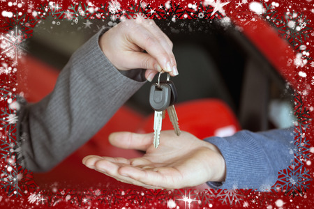Composite image of person handing keys to someone else against snow photo