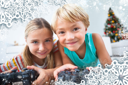 having fun in winter time: Composite image of happy siblings playing video games on floor against snow