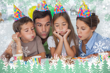 Composite image of family blowing candles together against snow photo