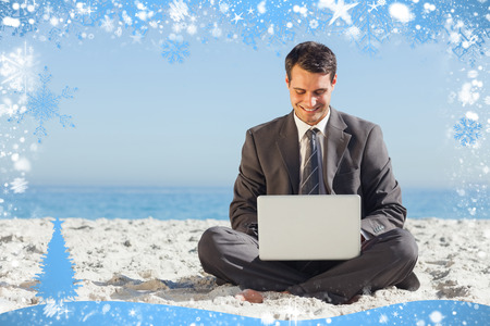 out of context: Young businessman with legs crossed typing on his laptop against snow
