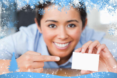 Composite image of attractive woman showing her visiting card against snow photo