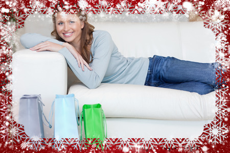 Woman relaxing on the sofa next to her shopping against snow photo
