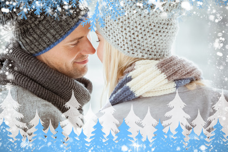 Composite image of couple in warm clothing facing each other against snow photo