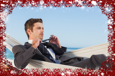 Composite image of snow frame against businessman man lying in hamock taking off his tie photo