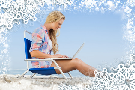 Pretty blonde sitting on beach using her laptop against snow photo