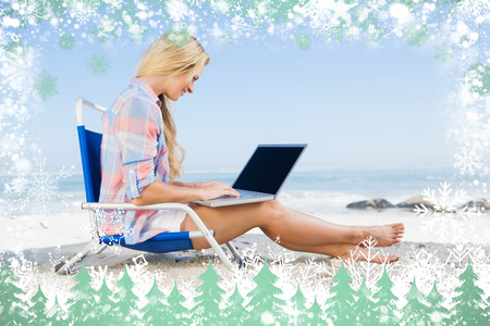 Woman sitting on beach using her laptop  against snow photo