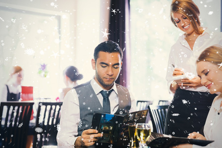 Composite image of two business people ordering dinner against snow falling photo