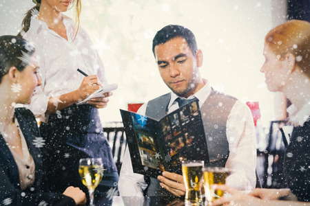 Handsome businessman ordering dinner from waitress against snow photo
