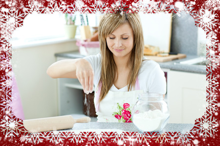 gratified: Portrait of a cute woman preparing a cake in the kitchen  against snow