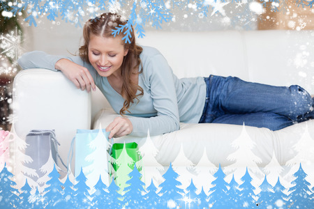 Young female on the sofa looking into her shopping bags against snow photo