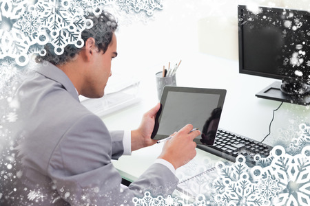 Businessman looking at his tablet in his office against snow photo