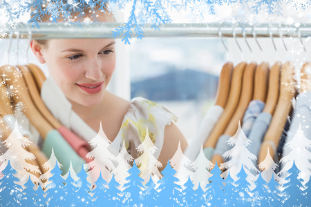 Female customer selecting clothes at store against snow photo