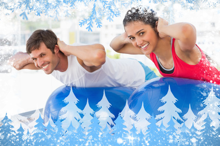 Fit couple exercising on fitness balls in gym against snow photo