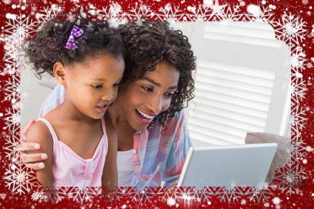 Cute daughter using laptop at desk with mother against snow photo