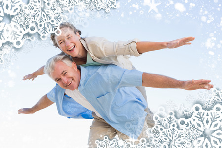 Composite image of happy casual couple having fun against snow photo