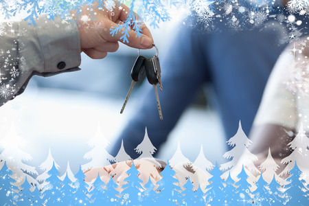 Composite image of car dealer giving keys to a customer against snow photo