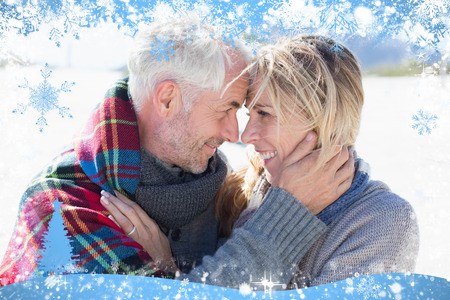 hair wrapped up: Happy married couple embracing on the beach against snow