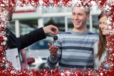 Composite image of couple receiving car keys by a dealer against snow photo