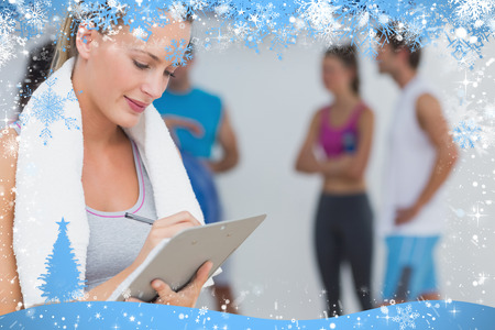 adult  body writing: Trainer writing on clipboard with fitness class in background at gym against snow
