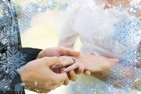 Composite image of snow frame against groom placing ring on brides finger photo