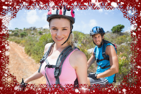 Fit couple cycling up mountain trail smiling at camera against snow photo