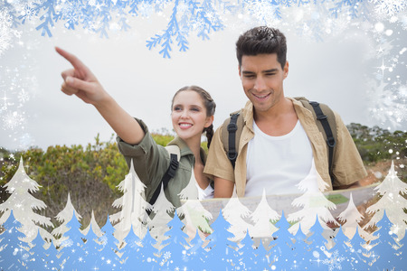 Couple with map pointing ahead on mountain terrain against snow photo