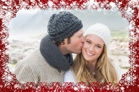 Composite image of snow frame against man kissing a woman on rocky landscape photo