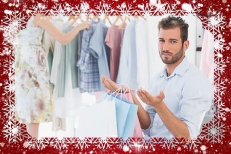 Bored man with shopping bags while woman by clothes rack against snow Stock Photo