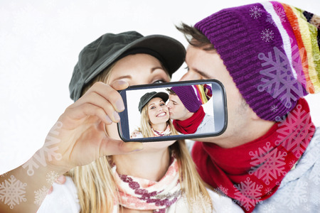 Hand holding smartphone showing photo against snowflake frame photo