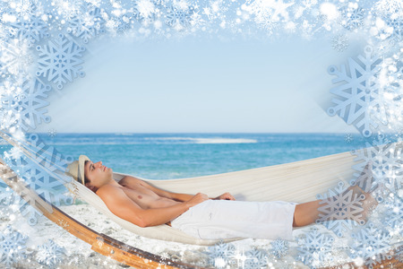 Composite image of snow frame against handsome man relaxing in a hammock photo