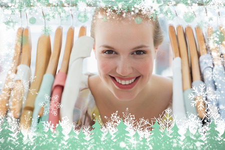 Happy female customer amid clothes rack against snow photo