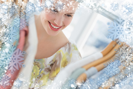 Beautiful female customer selecting clothes at store against snow photo