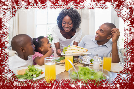 Happy family enjoying a healthy meal together  against snow photo