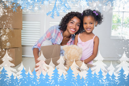 Cute daughter unpacking her teddy bear with mother against snow photo