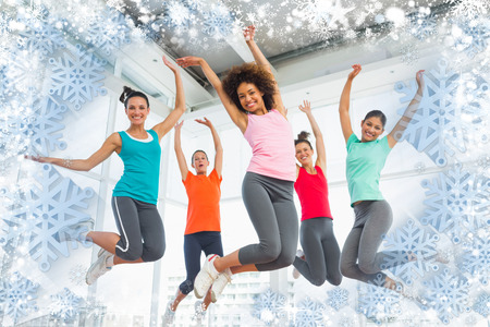Composite image of snow frame against fitness class and instructor jumping in fitness studio photo