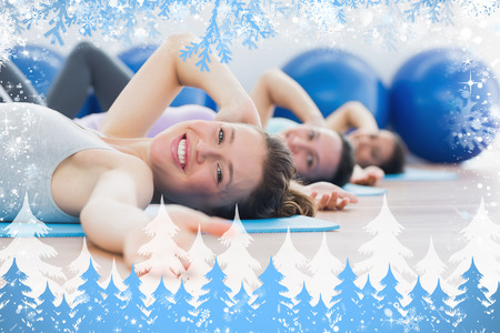Portrait of class exercising in row at fitness studio against snow photo