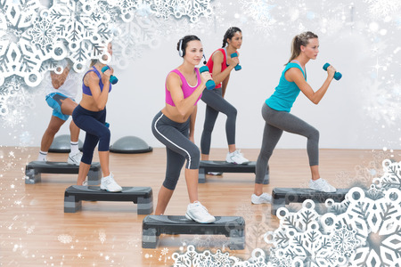 Fitness class performing step aerobics exercise with dumbbells against snow photo