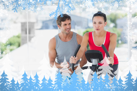 Woman with male instructor working out at spinning class against snow photo